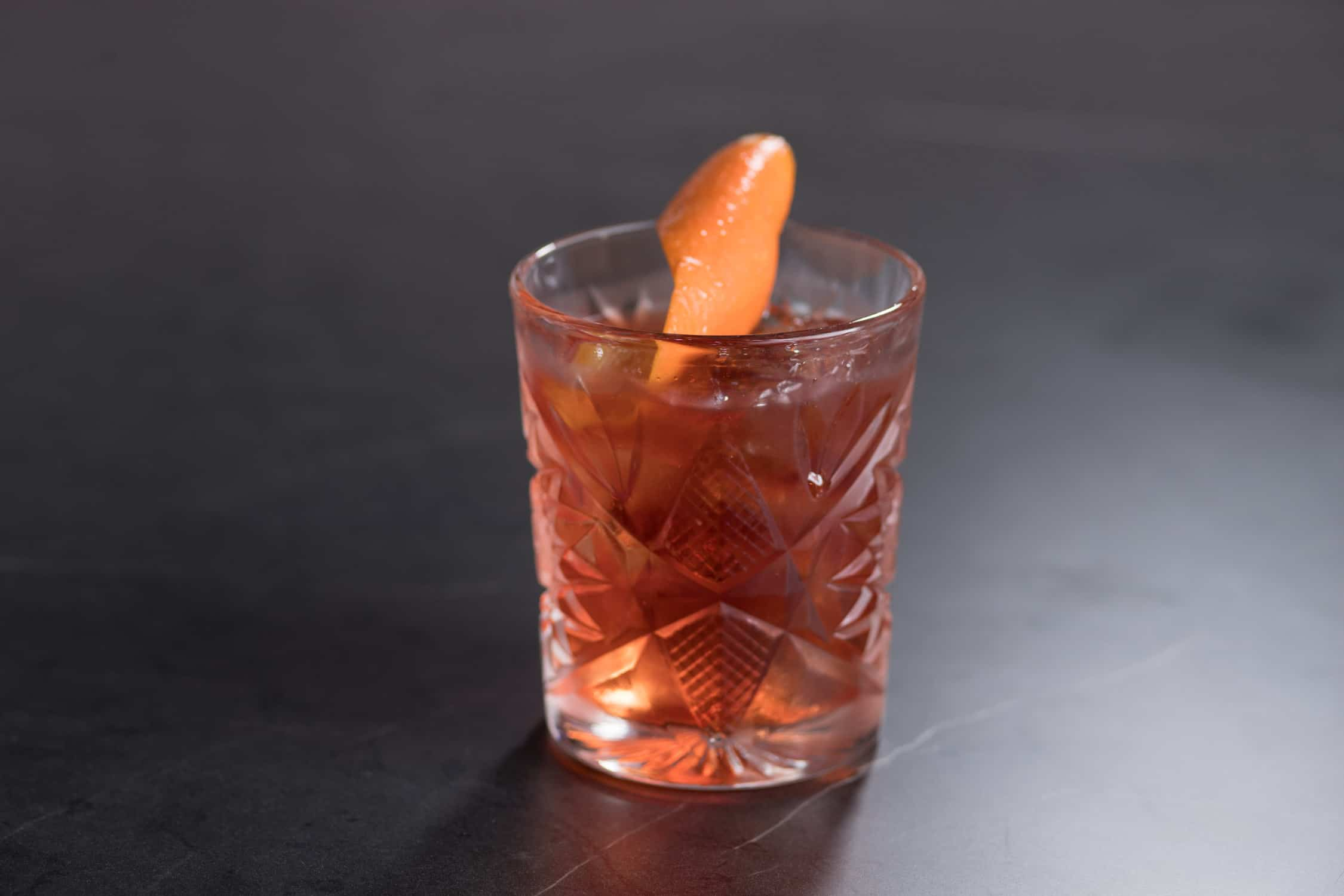 Cocktail with orange swirl served at Saros Bar